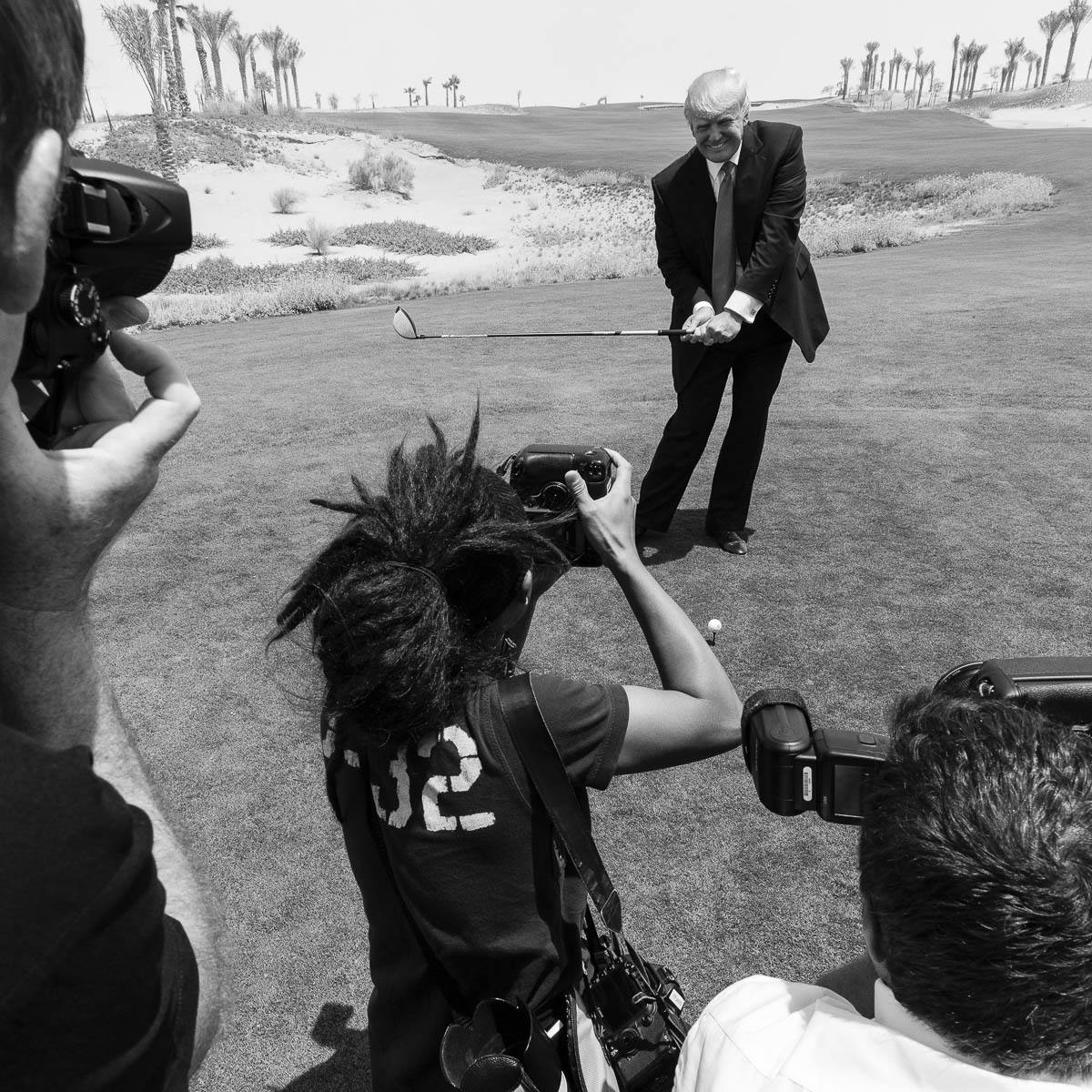 Donald Trump takes a practice swing for photographers on the Akoya golf course in Dubai