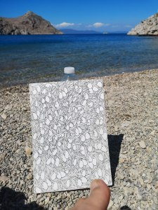 Drawing olives on the beach in Symi