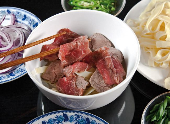 укладка сырой говяжьей вырезки в тарелку для супа по-ханойски фо-бо