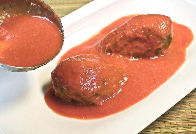 добавление соуса к баклажанам на сервировочной тарелке