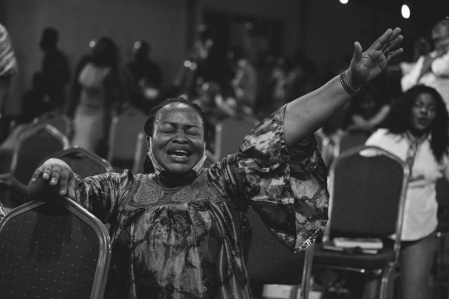 Woman on her knees worshipping God under Dunsin Oyekan's ministration