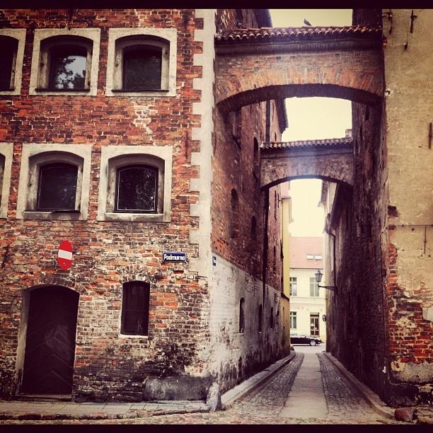 Ulica Ciasna w Toruniu. Malownicza najwęższa gotycka uliczka Torunia w pobliżu ruin zamku krzyżackiego