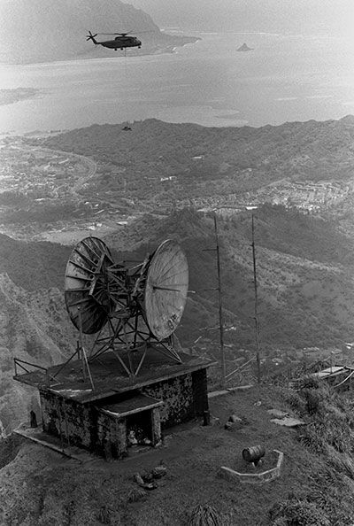 A U.S. Marine Corps Sikorsky CH-53D Sea Stallion helicopter from Marine Heavy Helicopter Squadron 463 (HMH-463) transports a winch to the Coast Guard Kaneohe Omega Transmitter, Haiku Valley, Oahu, Hawaii (USA), in 1987.