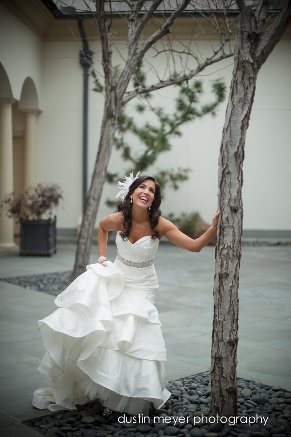 A laughing bride leaning against a tree while holding her bridal gown.