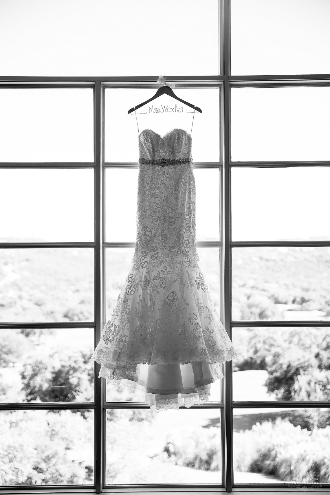 black and white image of a gorgeous strapless lace bridal wedding gown hanging in the window backlit