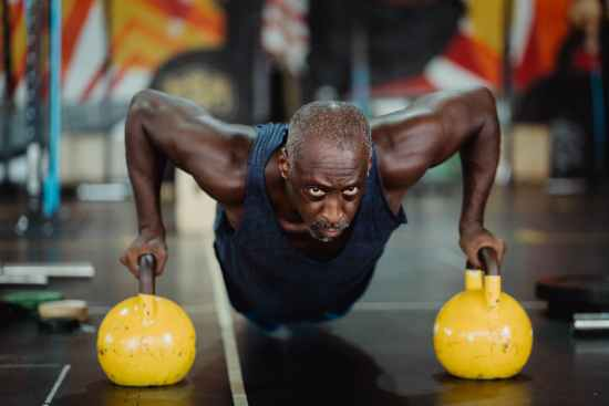 photo of man doing push ups using yellow kettlebell