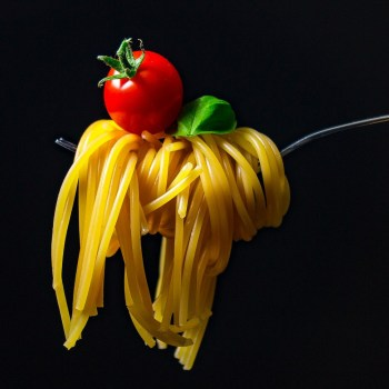 Pasta curled around a fork with a tomato