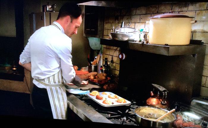 Jonny Lee Miller as Sherlock Holmes cooks Yorkshire puddings in the series Elementary