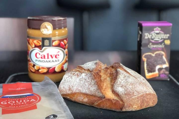 Stuk zuurdesembrood met eromheen een pak chocoladehagelslag van De Ruijter, een grote pot Calvé pindakaas en Gouda kaasplakken van de Britse Aldi