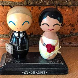 wooden figurines representing Zarina and her husband in their wedding attires