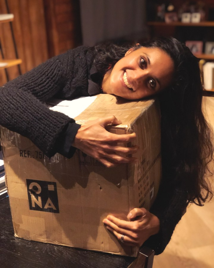 Zarina looking happy hugging a large parcel filled with Dutch food