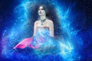 An image of a woman seated in amidst a blue aura, looking upwards