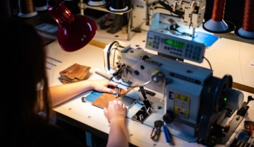 A Duvall Leatherwork artisan stitches together a quality leather wallet.