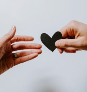 One hand handing a black cutout of a heart to another hand