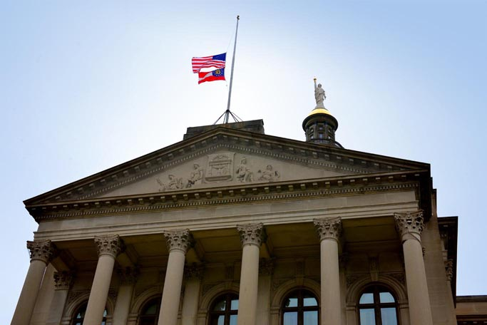 U.S. and Georgia flags fly at the Georgia Capitol. (Flags pictured flew half-staff on December 8, 2012.)