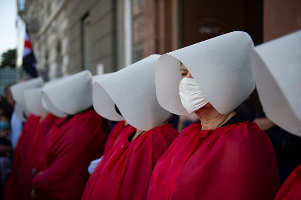 Demonstrators wearing protective face masks are dressed as the Handmaids from the dystopian novel The Handmaid's Tale from the Canadian author Margaret Atwood perform during an anti-domestic violence protest on July 24, 2020 in Warsaw, Poland. Thousands of demonstrators took part in a protest against government plan to pull out of an international treaty on preventing and combating domestic violence.