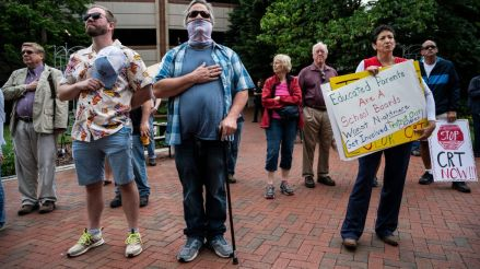 """People hold up signs during a rally against """"critical race theory"""" (CRT) being taught in schools at the Loudoun County Government center in Leesburg, Virginia on June 12, 2021. - """"Are you ready to take back our schools?"""" Republican activist Patti Menders shouted at a rally opposing anti-racism teaching that critics like her say trains white children to see themselves as """"oppressors."""" """"Yes!"""", answered in unison the hundreds of demonstrators gathered this weekend near Washington to fight against """"critical race theory,"""" the latest battleground of America's ongoing culture wars. The term """"critical race theory"""" defines a strand of thought that appeared in American law schools in the late 1970s and which looks at racism as a system, enabled by laws and institutions, rather than at the level of individual prejudices. But critics use it as a catch-all phrase that attacks teachers' efforts to confront dark episodes in American history, including slavery and segregation, as well as to tackle racist stereotypes."""