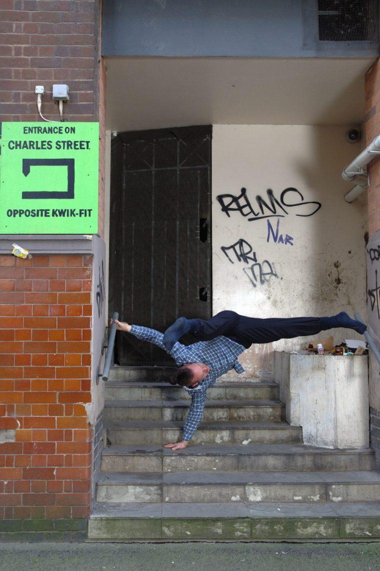 Ian Dolan, man contemporary dancing in the street in front of a door