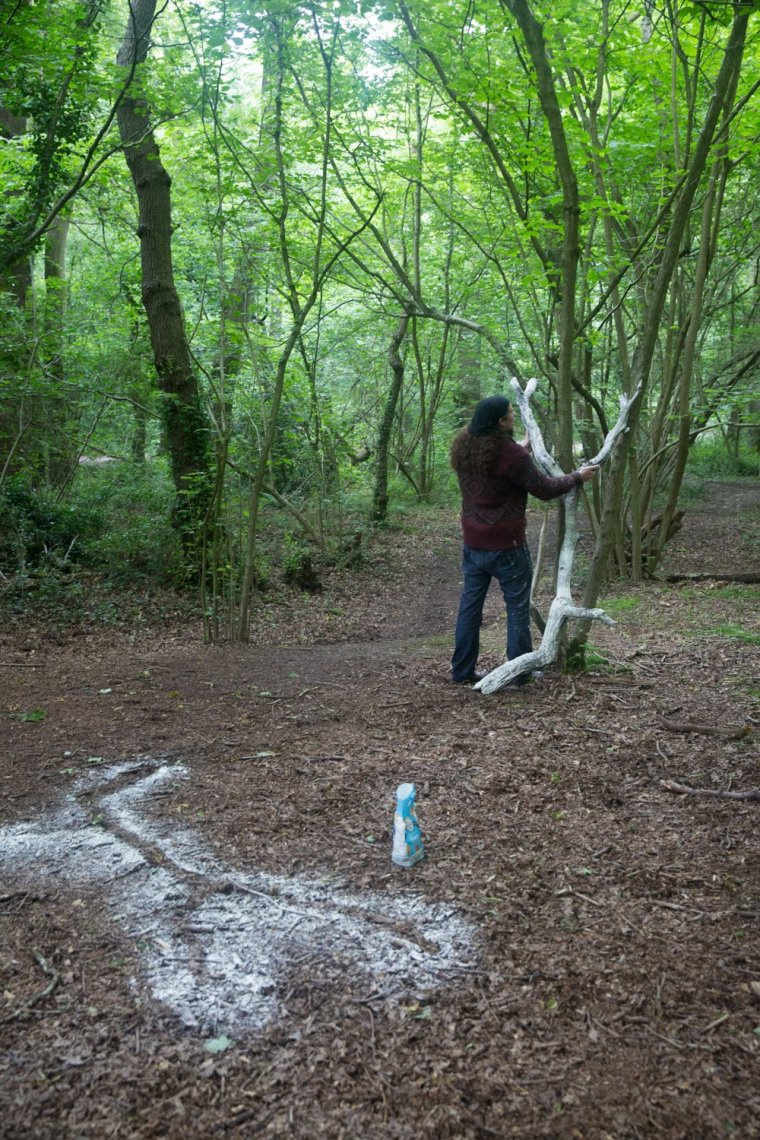 Matt Smith leans a branch white with flour against a tree