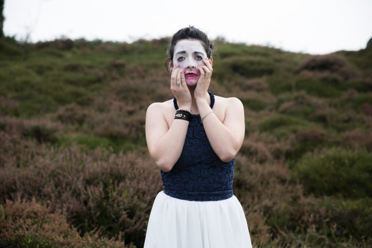 Emma Chatel dressed elegantly, with white painted makeup stands in grassland unhappily clawing at her makeup