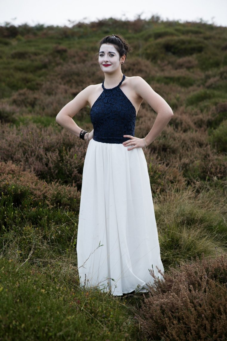 Emma Chatel dressed elegantly, with white painted makeup stands in grassland with a forced smile