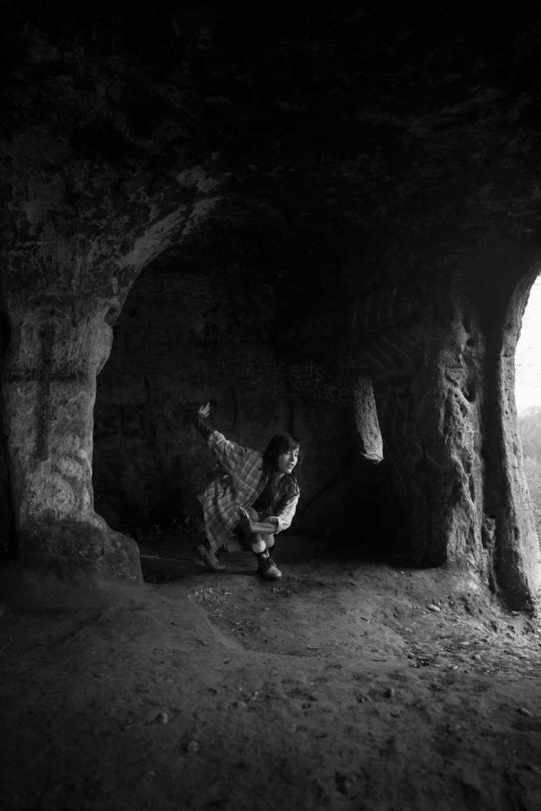 Black & white photo of Laura dancing in a cave