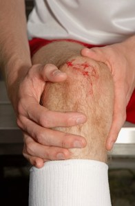 Soccer Player Holding Injured Knee --- Image by © Royalty-Free/Corbis