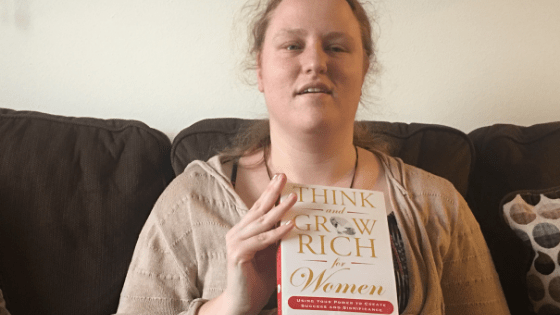 """Katie Corbett holds the book, """"Think and Grow Rich for Women"""""""