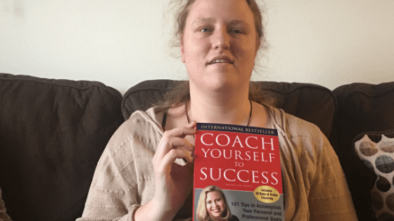 """Katie Corbett holds the book """"Coach Yourself to Success"""" by Talane Miedaner."""