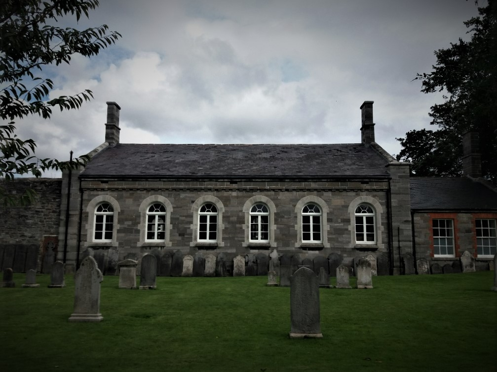 Headstones against the old garrison schoolhouse in Arbour Hill Cemetery Dublin