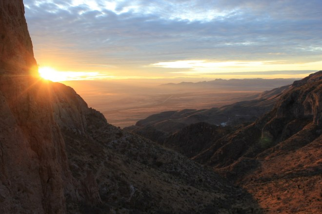 Photo of West Texas landscape with sun rising over a ridge in the foreground