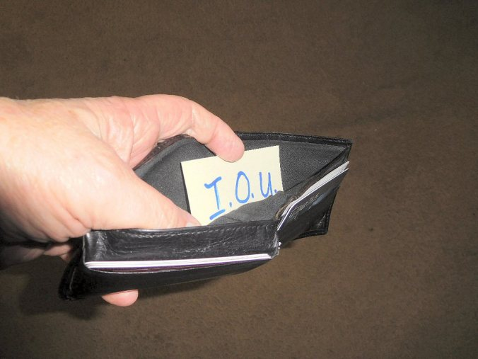 Photo of an empty wallet with an IOU slip inside