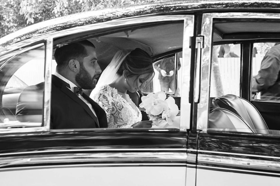 Lebanese couple just married riding in their vintage wedding day car