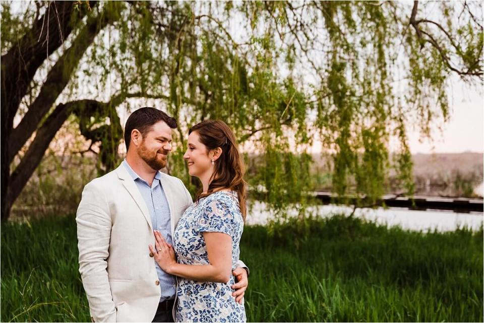 man and woman embracing under a willow tree - London Stratford Cambridge Woodstock Wedding Photographer by Dylan and Sandra of Dylan Martin Photography