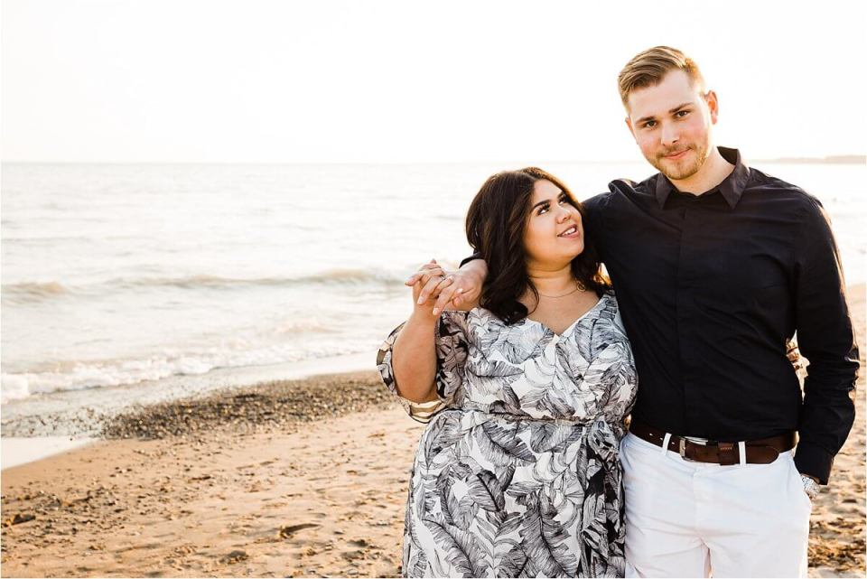 man with arm around woman's shoulder while walking on the beach - London Stratford Cambridge Woodstock Wedding Photographer by Dylan and Sandra of Dylan Martin Photography