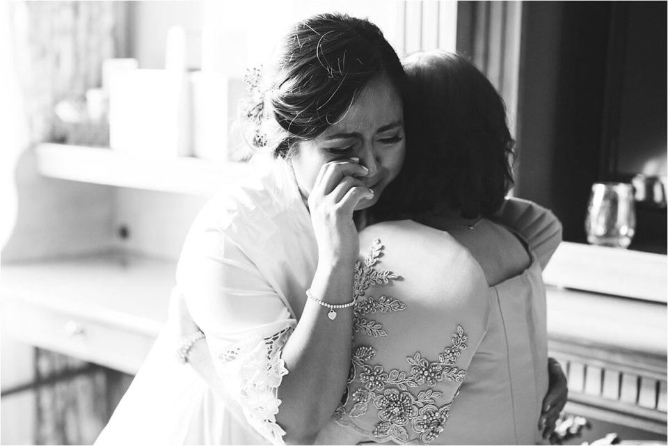 Bride crying on her mom's shoulder on her wedding day Dylan and Sandra of Dyan Martin Photography for Weddings and Engagement candid photographer in London, Cambridge, Stratford and Woodstock Ontario