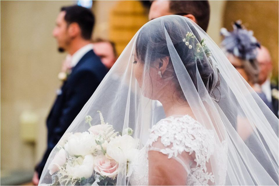 beautiful bride walking down the aisle wearing a long veil - Dylan and Sandra of Dyan Martin Photography for Weddings and Engagement candid photographer in London, Cambridge, Stratford and Woodstock Ontario