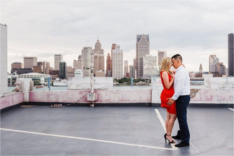 Couple cuddle close together on a parking garage overlooking the river