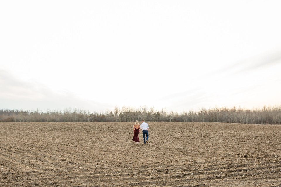 Engaged man and woman walking across the field hand in hand