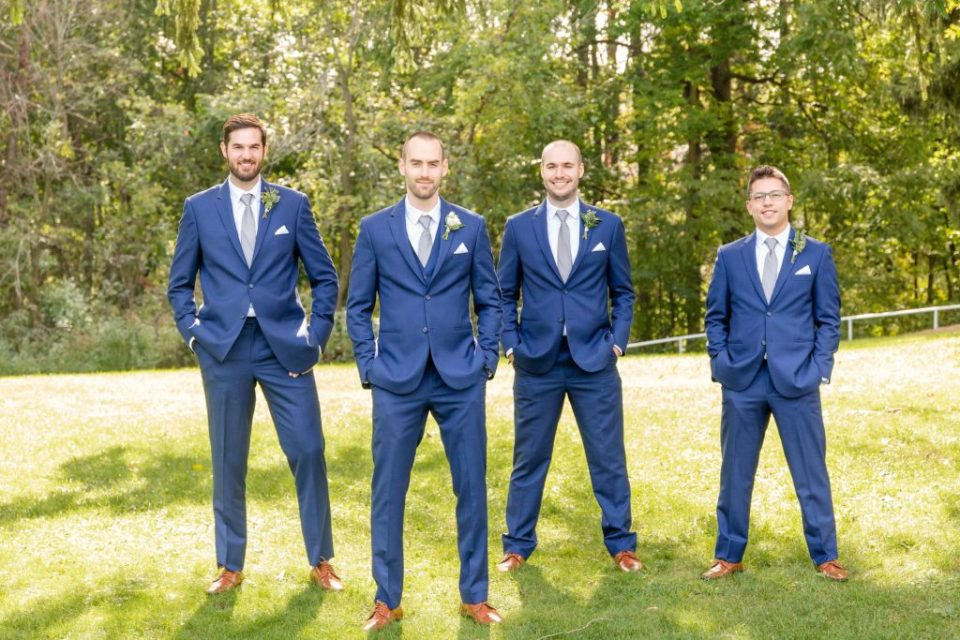Groomsmen standing with the groom outside on the property of Windermere Manor