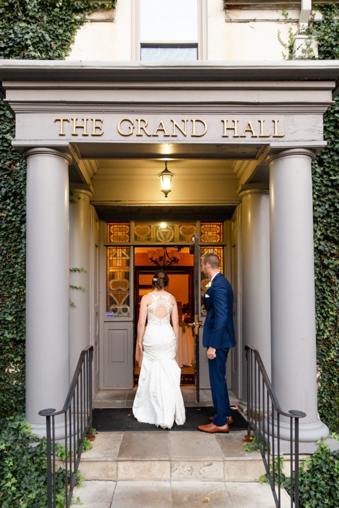 Groom holds the door open for his new wife as they enter their Windermere Manor reception