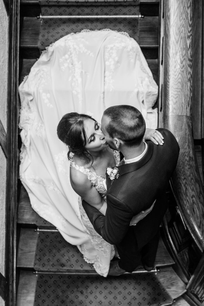 Couple kissing shot on the stairs at Windermere Manor from above
