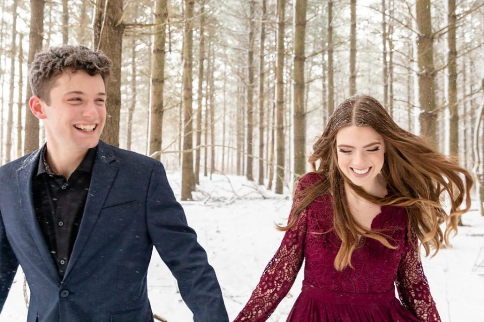 happy couple running in a pine tree forest for their winter engagement session