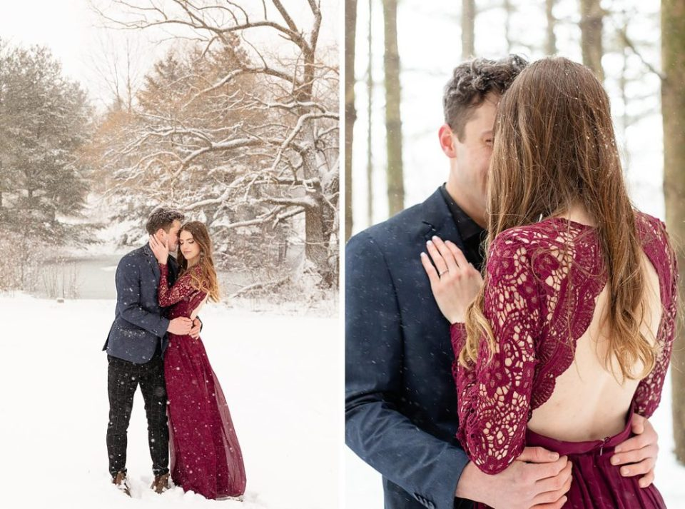 man in dress coat and woman in maxi lace dress embracing in the snow