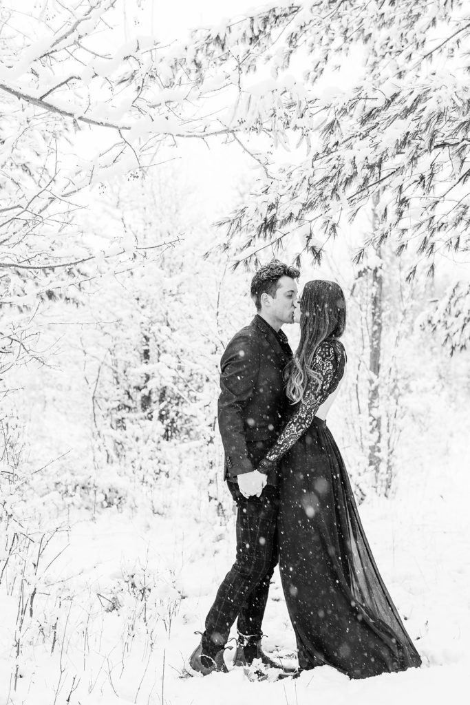 black and white winter photo of engaged couple kissing in the snow