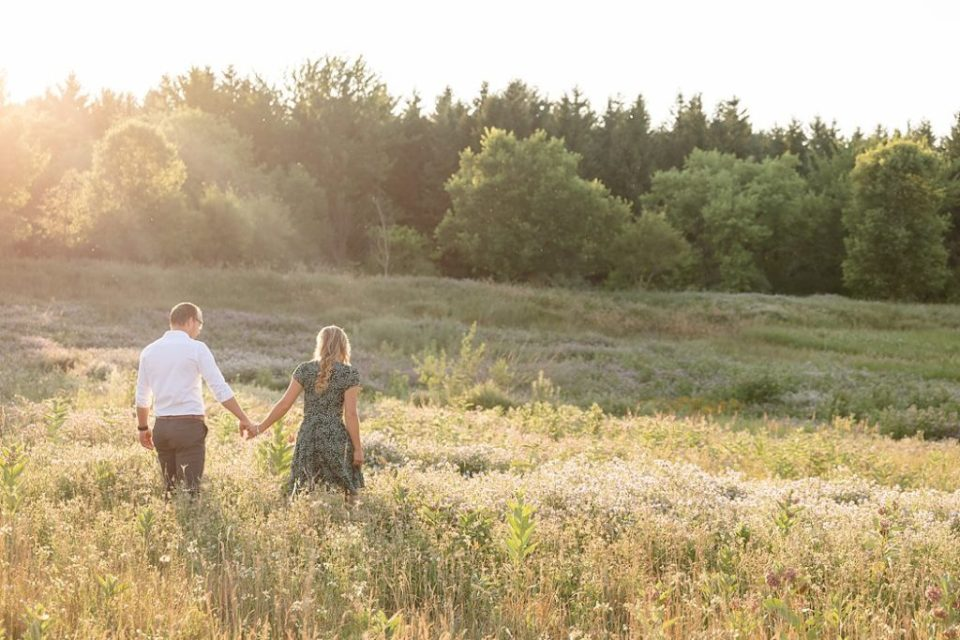Couple walking through field of flowers at Fanshawe Conservation Area