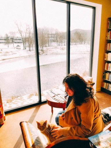 A girl sitting on the couch petting a cat in front of a window with a river outside