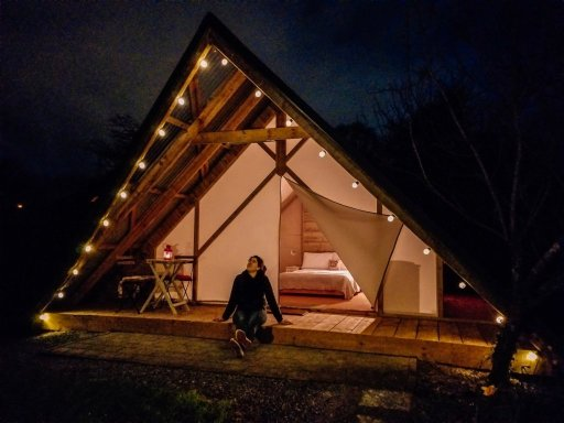Lit up, wooden A frame cabin at Killarney Glamping