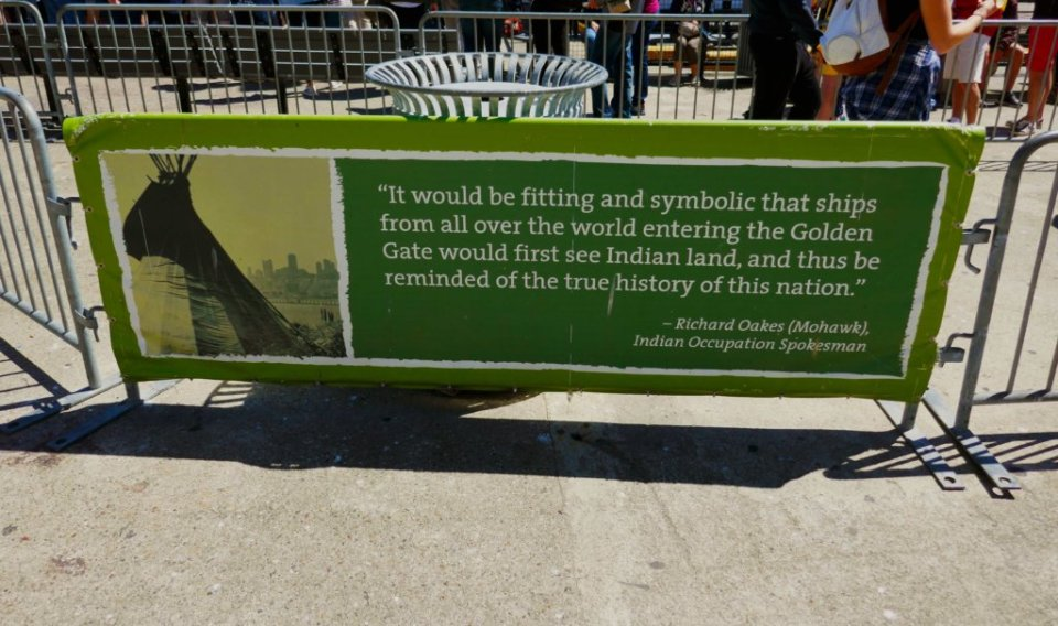Green sign with a quote from Richard Oakes about Indian Land