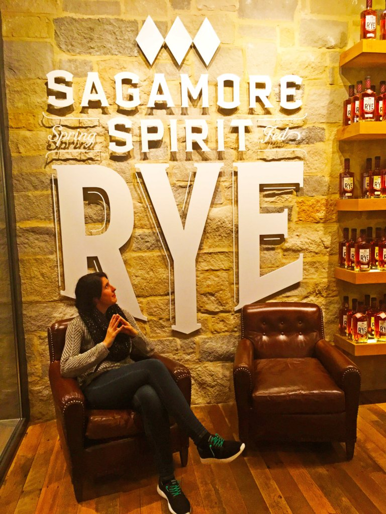 A young woman sitting in a leather chair in front of a sign that says Sagamore Spirit Rye